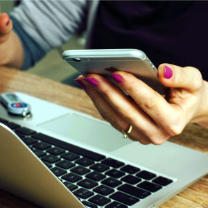 Flicka använder smarttelefon och dator.