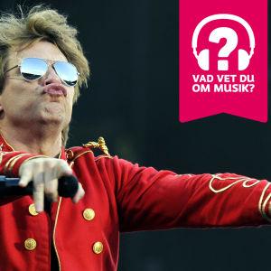 Jon Bon Jovi iklädd solglasögon. Han putar med läpparna, har händerna utsträckta framåt med en mikrofon i höger hand.