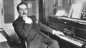 Giacomo Puccini sitter vid sitt piano