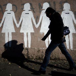 En kvinna går förbi en mur med målade kvinnofigurer.