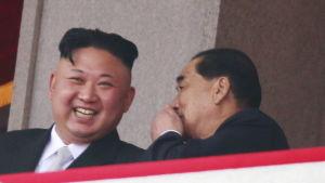 Någon viskar i Kim Jong Uns öra. Han skrattar.