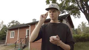 Nuori mies katselee epäileväisen näköisenä sormiensa välissä olevaa pienen pientä hyönteistä. Toisessa kädessä on pieni kuppi.