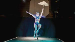 Sirkustaiteilija Jiohanna Kohonen yksipyöräisellä, kädessään päivänvarjo