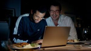 Christian (Claes Bang) och hans kollega Michael (Christoffer Læssøe) sitter vid en laptop och skrattar.