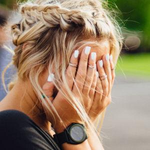 Nainen peittää kasvonsa käsillään