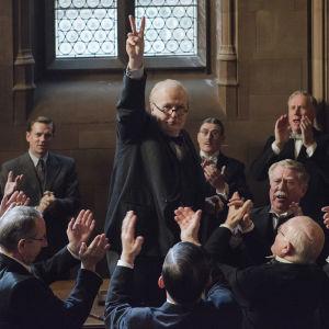 Winston Churchill (Gary Oldman) går segertecknet omringad av en massa människor.