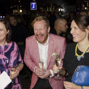 En man står mellan två kvinnor. Han skrattar stort.