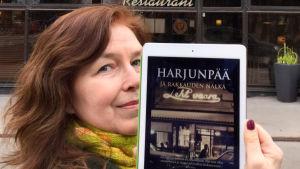 Kirjabloggaaja Tuijata kirja Harjunpää ja rakkauden nälkä kädessään
