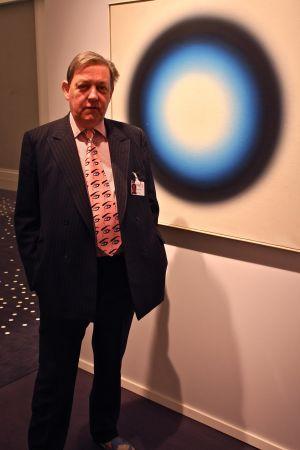 James Mayor poserar bredvid ett  Op-art konstverk från 1963 av polacken Wojciech Fangor. Lägg märke till Mayors kravatt.