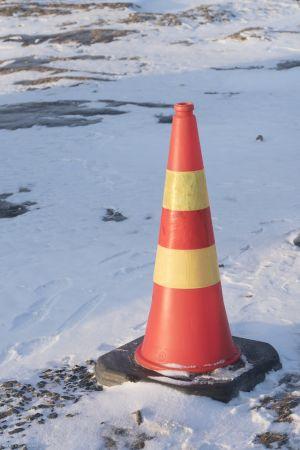 Kuminen kirkkaan oranssi liikenteenohjauskeila yksinään pakkasessa lumisella tasangolla. Aurinko valaisee mutta kylmä fiilis.