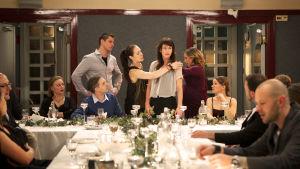 Scen ur filmen Återträffen där Anna Odell står vid ett festbord omringad av klasskompisar.
