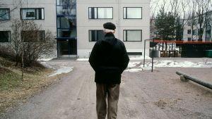 Äldre man går på gården