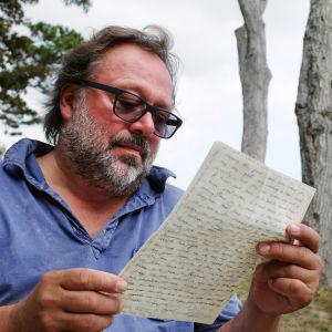 Dick Holmström läser ett brev från sin mamma.