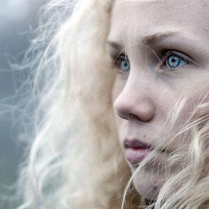 Karaktären Tyra i närbild med lockigt hår och kallblå ögon.