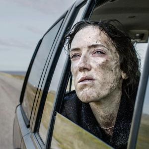 Karaktären Hedda sticker ut huvudet genom nervevad fönsterruta.