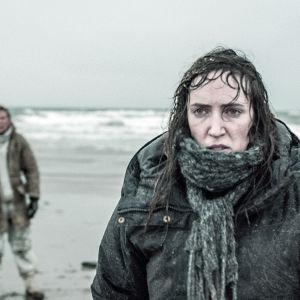 karaktären hedda smutsig och våt på en strand med havet i bakgrunden.