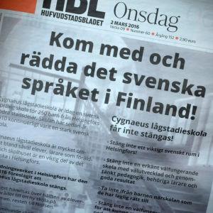 """En bild på en tidnings förstasida med texten """"Kom med och rädda det svenska språket i Finland!"""""""