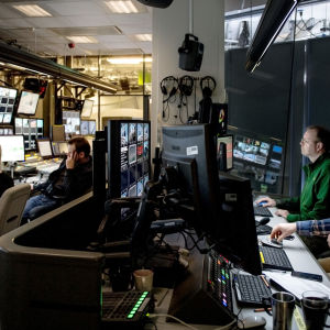 Uutisstudion ohjaamo, neljä ihmistä ja näyttöjä.