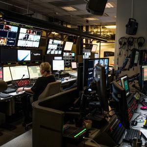 huone jossa tv-ruutuja ja ihmisiä istumasa niiden ääressä