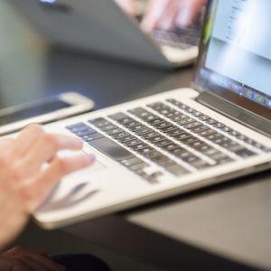 Lähikuva kannettavasta tietokoneesta ja älypuhelimesta.