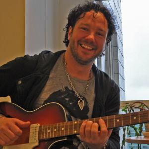 Jimmy Westerlund poserar med en Lucky 7 gitarr.