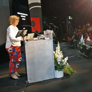 Anna-Maja Henriksson står bakom ett podium inför en publik i ett auditorium.