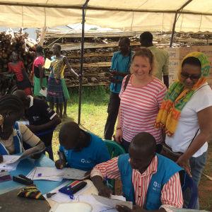 Afrikassa pakolaisleirilla kirjataan saapuneita pakolaisia katoksen alla. Maria Immonen seuraa vierestä