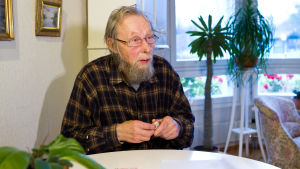 mies istuu pöydän äärellä