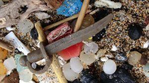 Ett litet legosvärd som ligger bland annat plastskräp på en sandstrand.