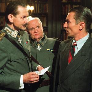 Vasemmalla Asko Sarkola, joka esittää Mannerheimiä. Takana keskellä Oiva Lohtander, joka esittää Walldenia. Äärimmäisenä oikealla on Robert Enckell, joka esittää eversti-luutnantti Josef Veltjenssiä.
