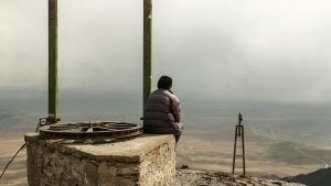 Samuel sitter och betraktar de kala glaciärerna i Bolivia.