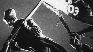Mies kantaa kivääriin ripustettua vallankumouksellista viiriä. Kuva Sergei Eisensteinin elokuvasta Lokakuu
