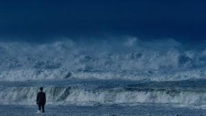 En ensam man står inför en enorm svallvåg som rullar in mot stranden.