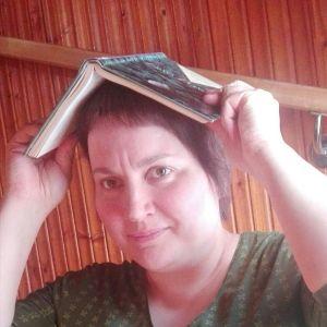 Kirjakko ruispellossa -blogin Mari Saavalainen pitää kirjaa päänsä päällä.