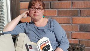 Kirjojen keskellä -blogin kirjoittajaa lukee parvekkeella Simpauttajaa.
