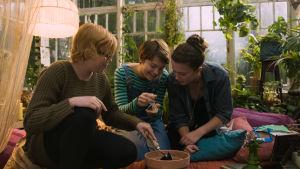 Bella, Kim och Momo sitter på golvet i ett växthus och planterar ett frö i en kruka.