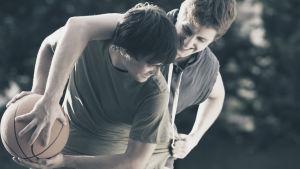 två killar spelar korgboll