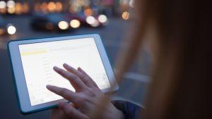 En kvinna håller i en datortablett med touchscreen på en mörk stadsgata.