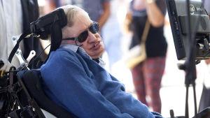 Närbild på Stephen Hawking ute i solskenet med solglasögon.