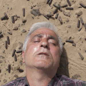 Saeid Sadeghi ligger i sanden omgiven av patronhylsor.