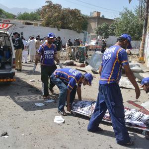 Räddningspersonal lyfter upp en bår till en ambulans i Quetta, Pakistan.