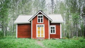 Punainen vanha puutalo jossa keltainen ovi, keskellä metsäaukeaa.
