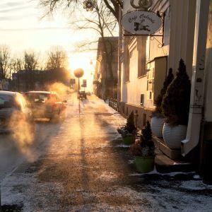 Solen lyser upp avgasen från bilen då den svänger bort från parkeringsplatsen.