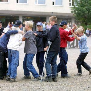 Ett gäng med pojkar står i en klunga på en skolgård.