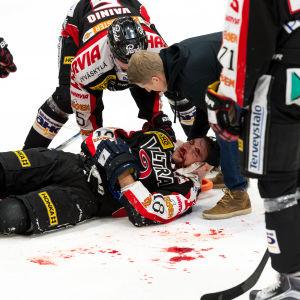 Michel Miklik ligger blodig på isen efter Joe Finleys tackling, januari 2017.