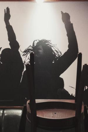 Restaurangbord med uppstaplade stolar, i bakgrunden ett fotografi av människor som dansar med händerna i luften.