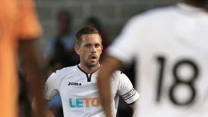 Gylfi Sigurdsson står på en fotbollsplan.