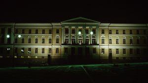 Helsingfors universitets huvudbyggnad upplyst på kvällen