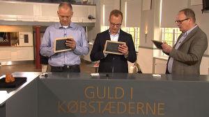 Tre värderare står vid ett bord och skriver sina bud på små tavlor.