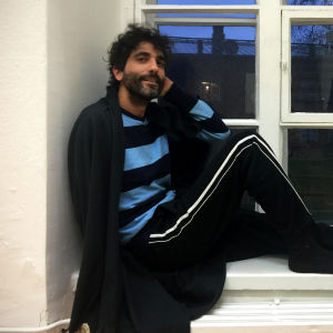 Bild på man som sitter i ett fönster, det är mörkt utanför.
